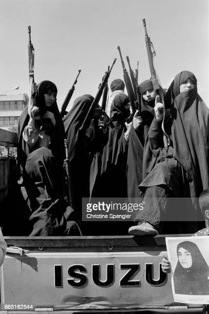 A group of women members of the Pasdarane Inqilab or Iranian Revolutionary Guard Corps hold rifles while standing in the back of a truck In May of...