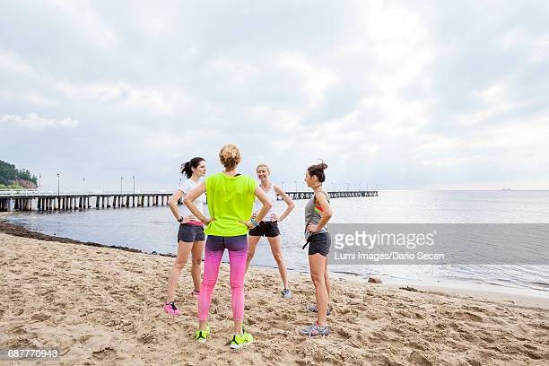 Group of women on beach doing warm up exercises