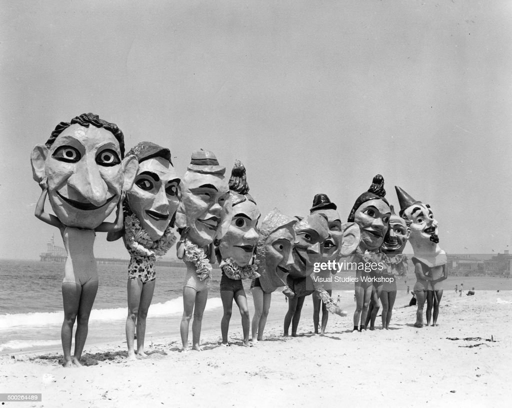 Group of women on the beach preparing for the Annual Venice Mardi Gras and Carnival wearing paper mache masks, Venice, California, early to mid 20th century.