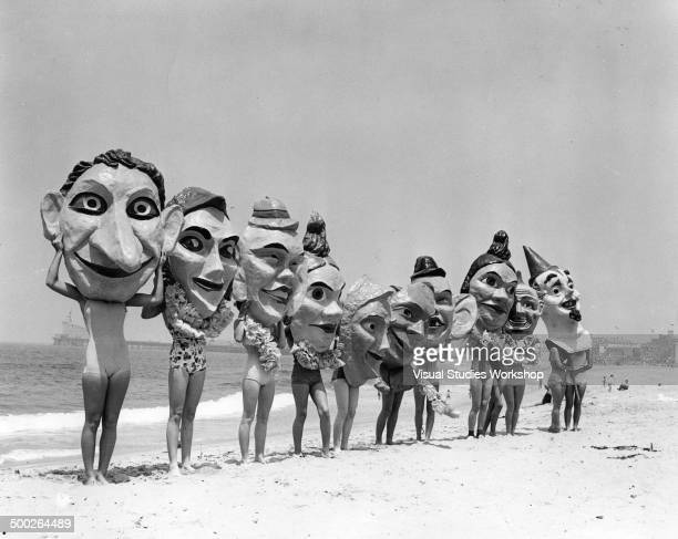 Group of women on the beach preparing for the Annual Venice Mardi Gras and Carnival wearing paper mache masks Venice California early to mid 20th...