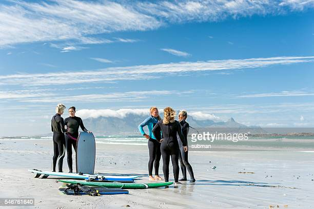 Group Of Women On The Beach With Surf Equipment