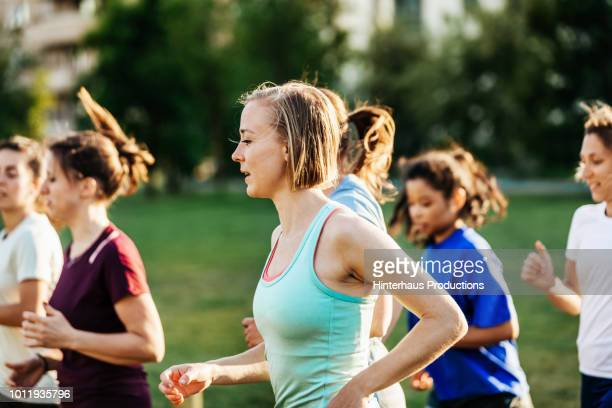 group of women out running together - public park stock-fotos und bilder