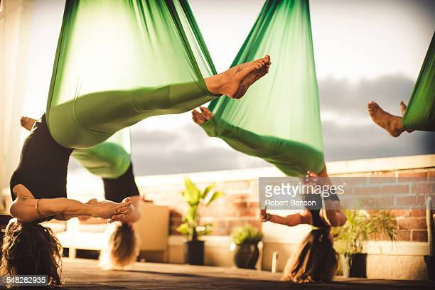 A group of women perform aerial yoga.