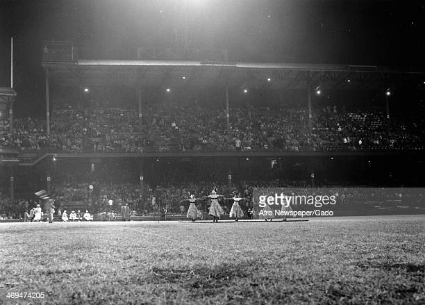 A group of women performing in front of the audience sitting in a large grandstand 1950