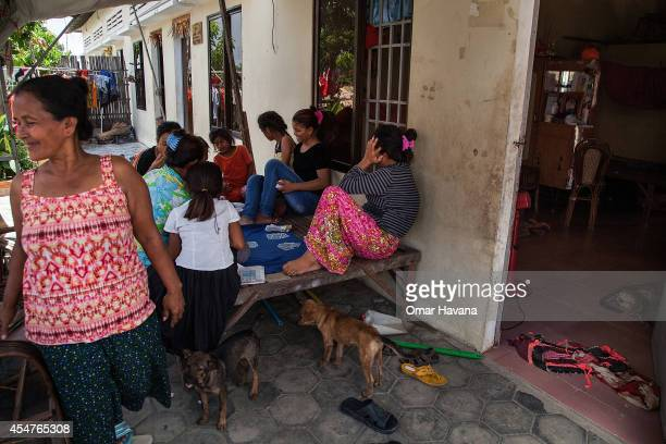 A group of women play card games outside one of their houses in the community on September 6 2014 in Tuol Sambo Cambodia Three different communities...