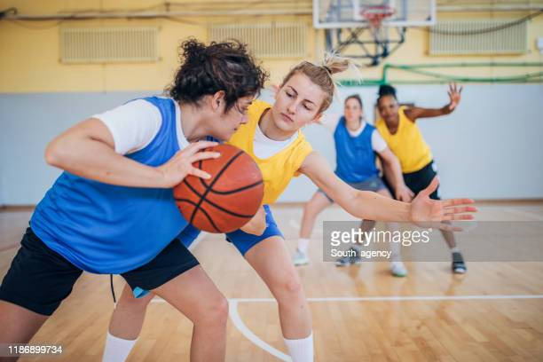group of women playing basketball indoors - women's basketball stock pictures, royalty-free photos & images