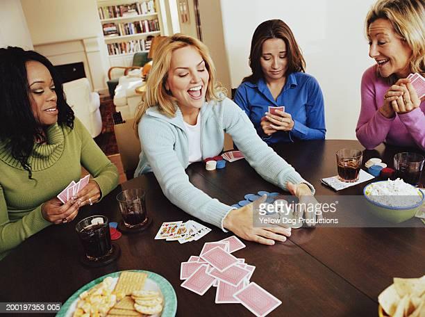 group of women playing cards, woman taking chips, smiling - poker - fotografias e filmes do acervo