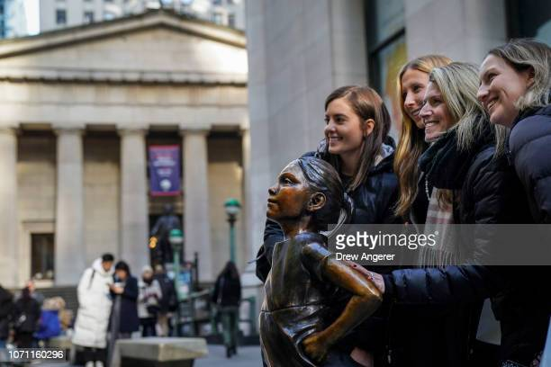 A group of women pose with the 'Fearless Girl' statue after a ceremony to unveil the statue's new location across from the New York Stock Exchange...