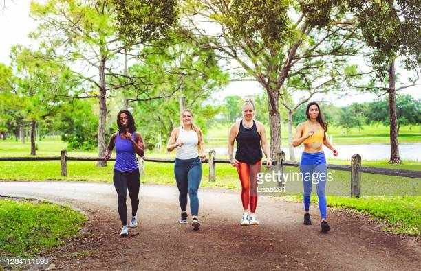 group of women power walking outdoors - competition group stock pictures, royalty-free photos & images
