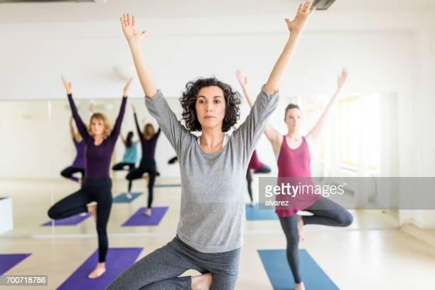 Groupe de femmes pratiquant avancé yoga au gym