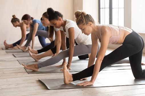 Group of women practicing yoga lesson, doing Ardha Hanumanasana exercise 1067864612