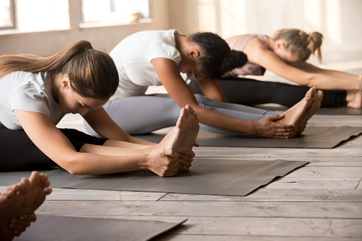 Group of women practicing yoga lesson in paschimottanasana pose 1076947090