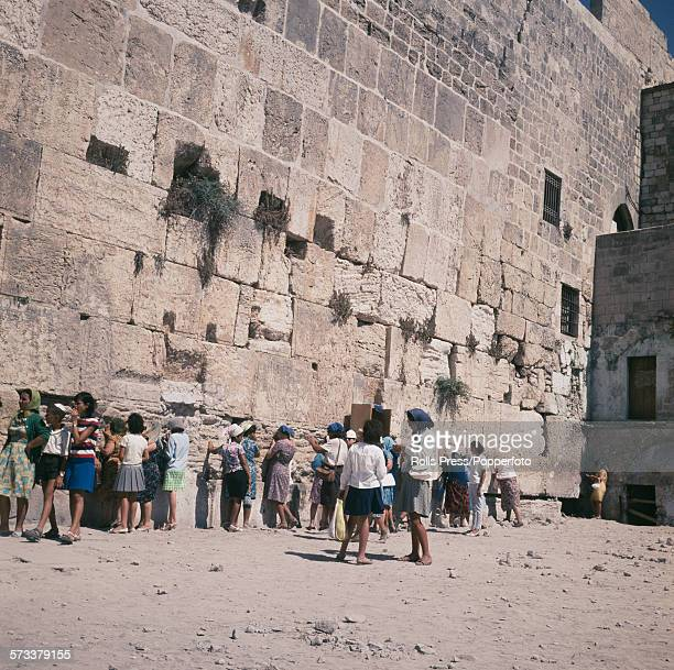 A group of women pray worship and congregate next to the Western Wall or Wailing Wall by the Temple Mount in Jerusalem Israel following the end of...
