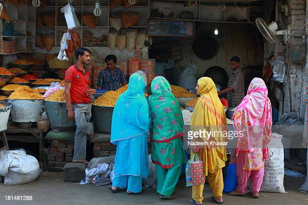 Group of women purchasing the grains for food from Akbari Mandi,Streets of Lahore. This image show the daily routine work of Down town and the...