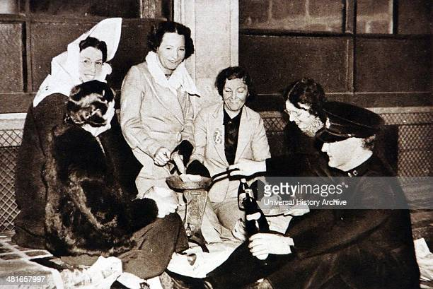 Group of women receive drinks from a Salvation Army man while cooking a meal on the streets of London waiting for the coronation of king George VI...