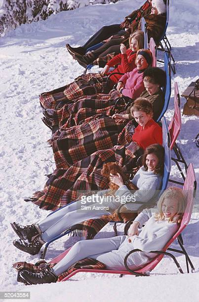 Group of women reclining on the snow in Gstaad with rugs covering their knees, 1963.