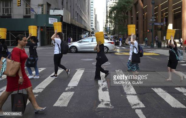 A group of women representing WaterAid's NYC 'Walk for Water' travel through midtown New York on July 16 2018 to show the daily lives of their peers...