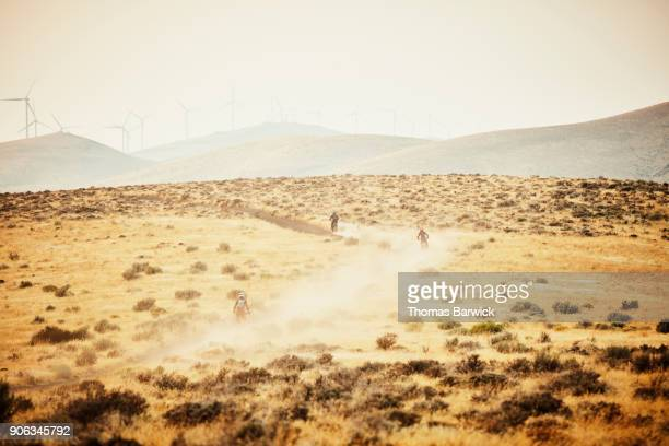 Group of women riding dirt bikes together on dusty desert road on summer evening