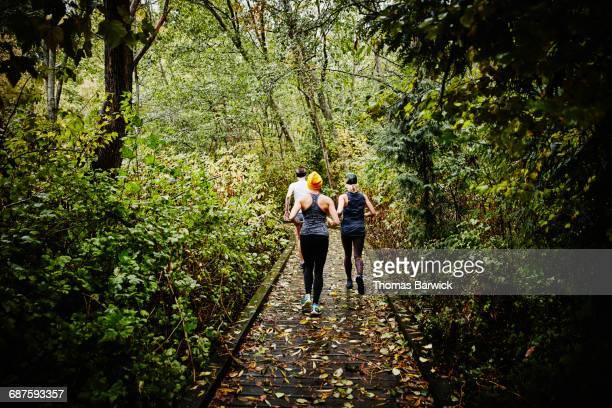 Group of women running on boardwalk through forest