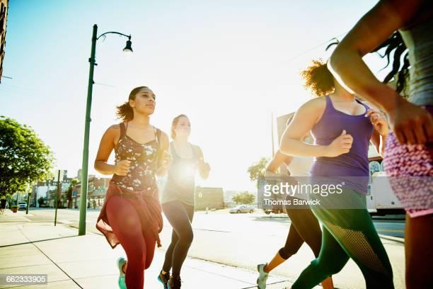 Group of women running on sidewalk at sunrise