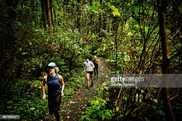 Group of women running on trail through forest