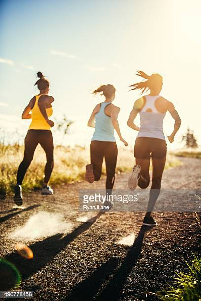 group of women running outdoors - verticaal stockfoto's en -beelden