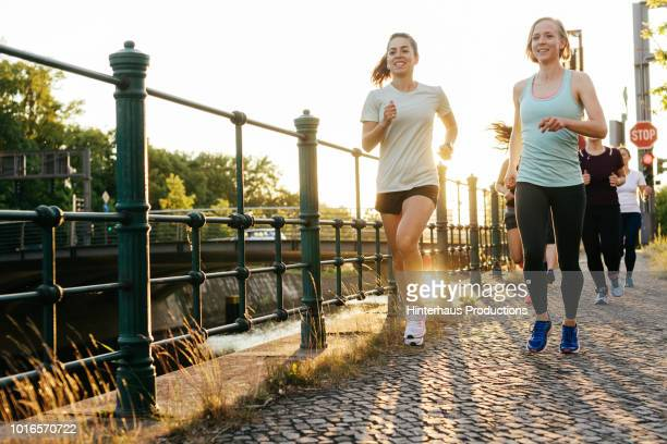 group of women running together alongside canal - jogging stock pictures, royalty-free photos & images