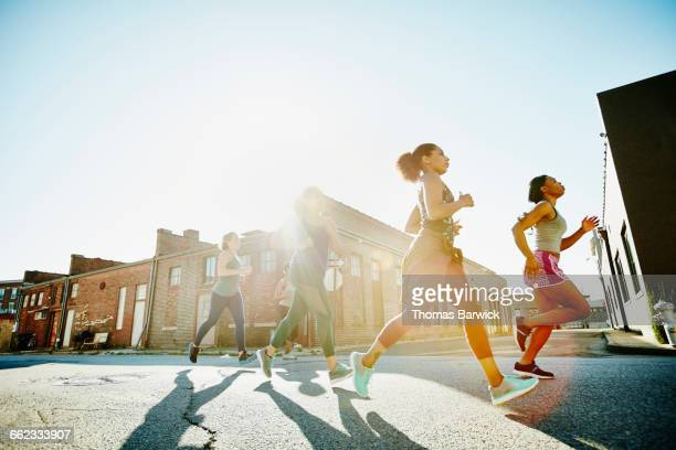 Group of women running together at sunrise