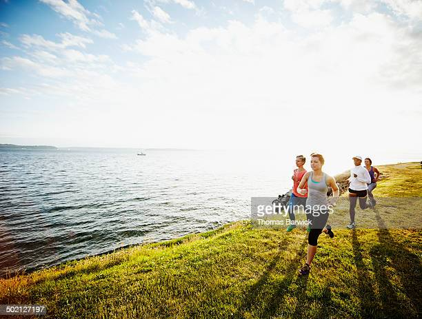 Group of women running together on grass at sunset