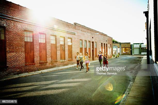 Group of women running together on urban street
