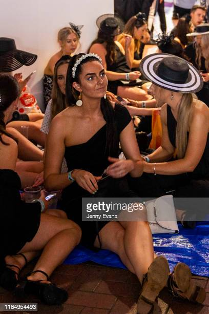 A group of women set up a picnic under the grandstand as rain falls during 2019 Derby Day at Flemington Racecourse on November 2 2019 in Melbourne...