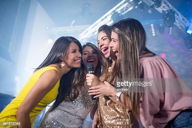 Group of women singing at a karaoke bar