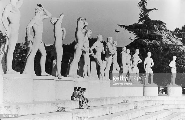 Group of women sitting beneath a row of large statues in the Rome stadium which has been prepared for the Olympics, 12th August 1960. The statues...