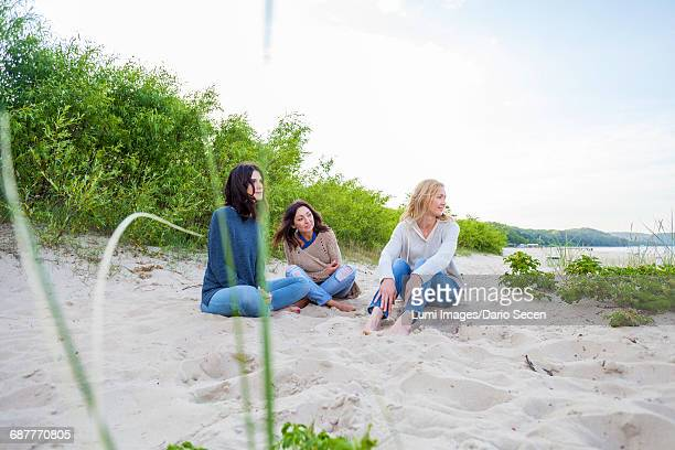 Group of women sitting on sandy beach