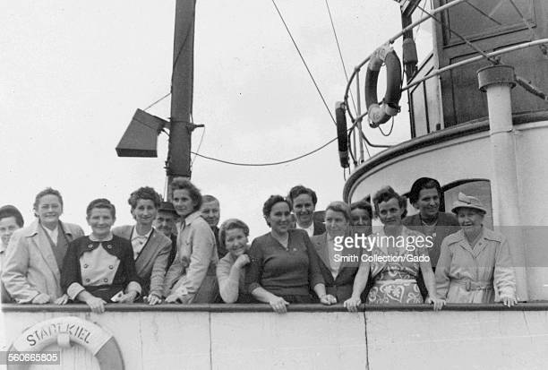 A group of women standing at the railing of a ship looking at camera smiling Kiel Germany 1946