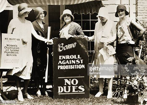 A group of women stands outside a house with signs inviting others to join their antiprohibition club