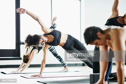 Group of women stretching before hot yoga class in fitness studio