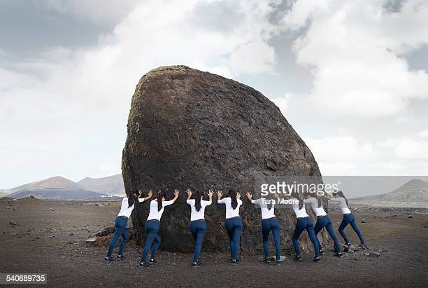 Group of women supporting a large rock