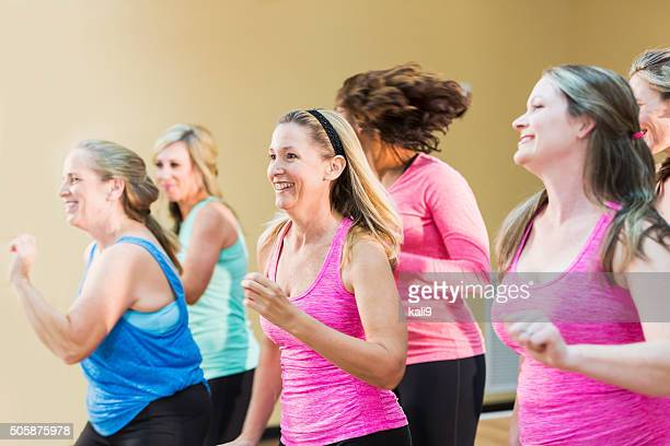group of women taking an exercise class - mid adult stock pictures, royalty-free photos & images