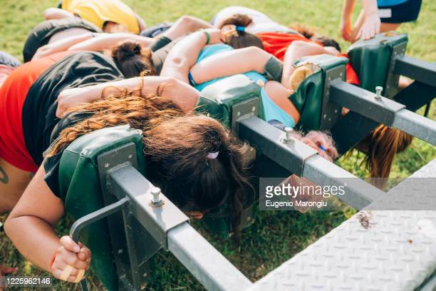 a group of women training to scrum against a machine on the training pitch. - rugby stock pictures, royalty-free photos & images