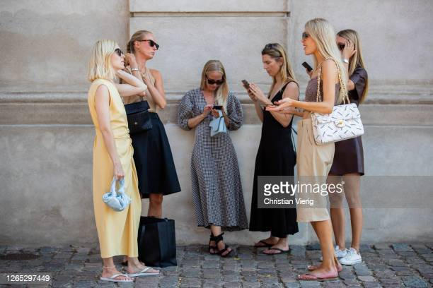 Group of women use their phones outside Remain Birger Christensen during Copenhagen Fashion Week Spring/Summer 2021 on August 11, 2020 in Copenhagen,...