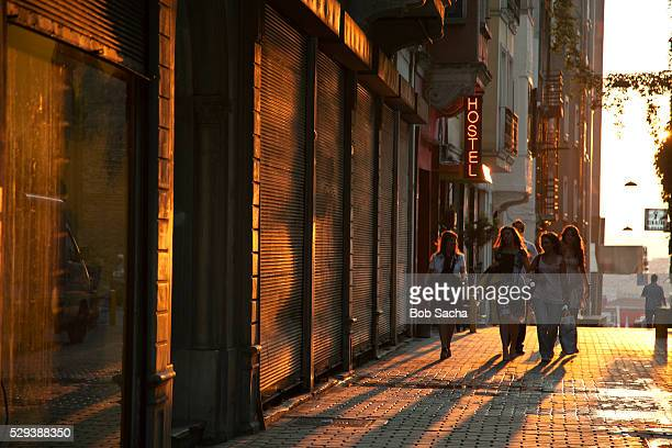 Group of women walk past a hostel at sunset, Istanbul, Turkey