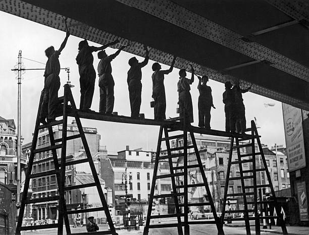 A group of women war workers painting a railway bridge...