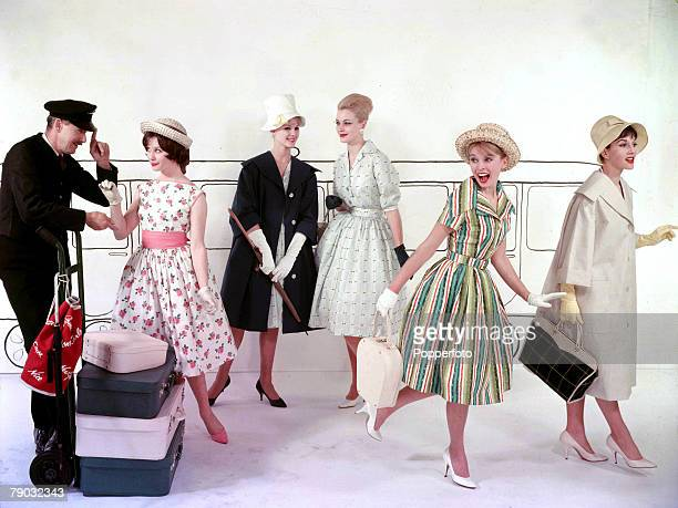 Group of women wearing a variety of summer dresses hats and lightweight coats in a studio mock up of a train station platform complete with a man...
