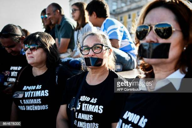 A group of women wearing black tshirts and with their mouths covered with black tape to show their support to the victims and animals killed during...