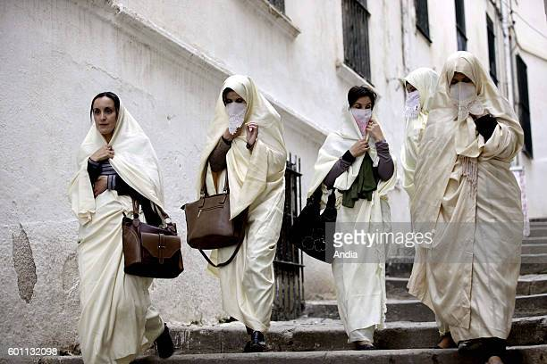 Group of women wearing haiks long white embroidered gowns Algerian women's traditional dress walking in a lane of Algiers kasbah