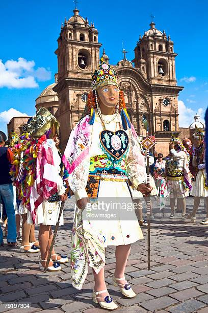 Group of women wearing traditional costumes and standing in front of a church, Peru