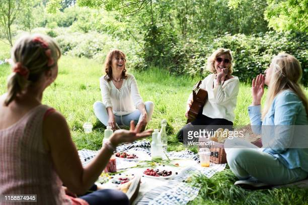 group of women with guitar having fun at a picnic in park - picnic stock pictures, royalty-free photos & images