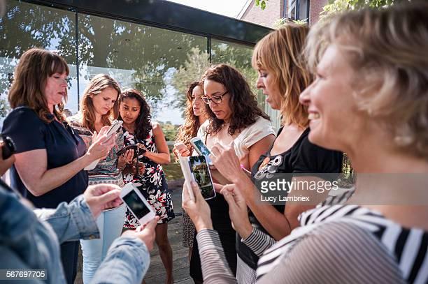group of women with their smartphones - grupo médio de pessoas - fotografias e filmes do acervo