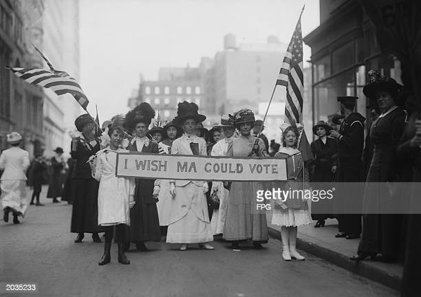 A group of suffragettes march in a parade carrying a banner reading 'I Wish Ma Could Vote' circa 1913